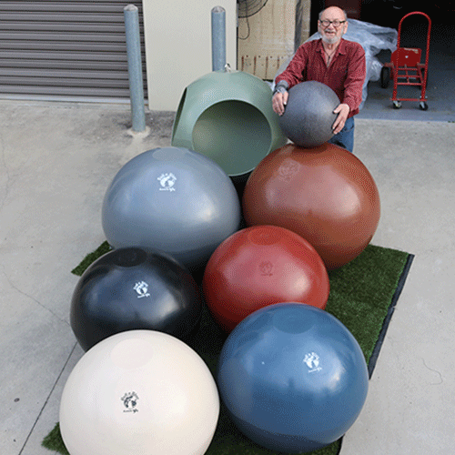 man standing with big plastic balls